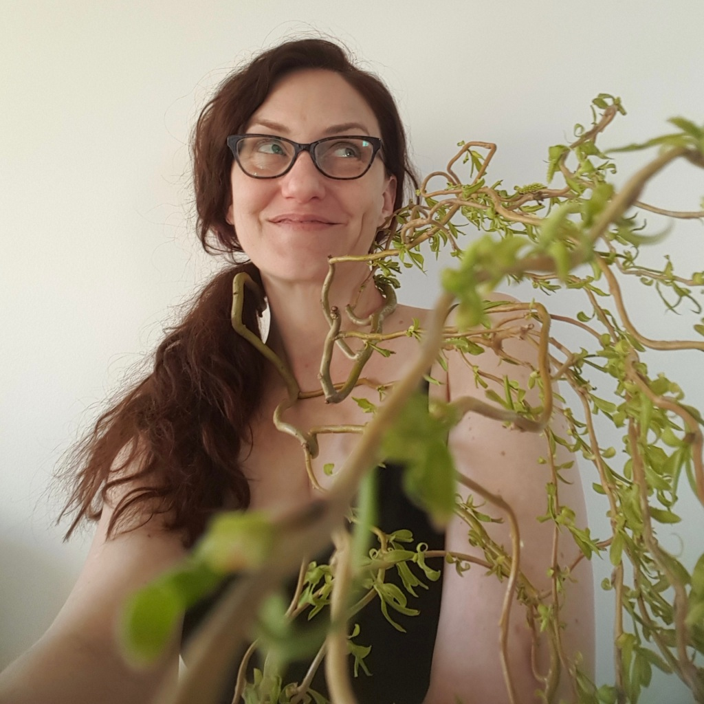 A picture of a woman wearing glasses, with a branch of a tree wrapped around her neck. The branch has pale green leaves.